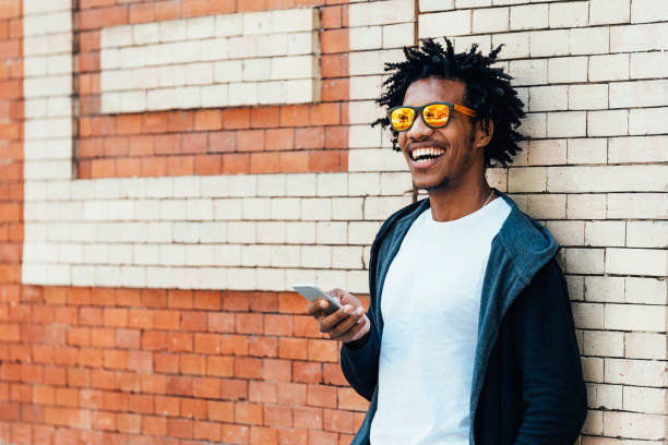Afro young man using mobile phone bicycle. stock photo