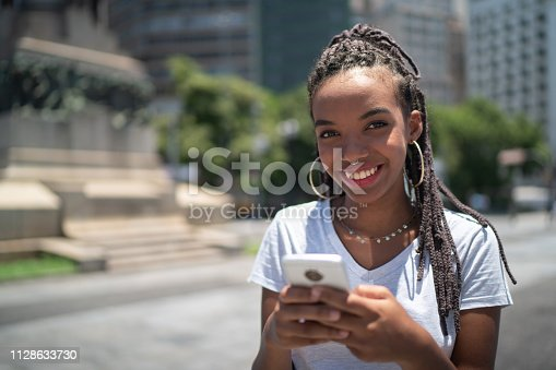 istock Afro young woman in the city using smartphone portrait 1128633730