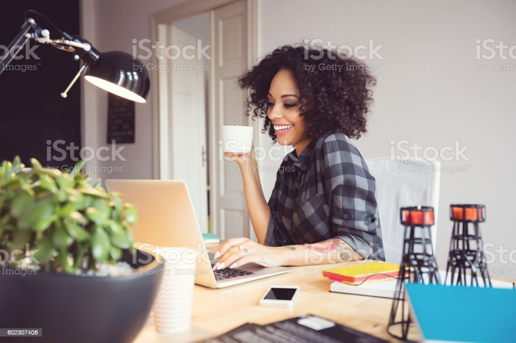 Afro young woman in the home office, using laptop Afro young woman sitting at the desk in a home office, using laptop, drinking coffee. Adult Stock Photo