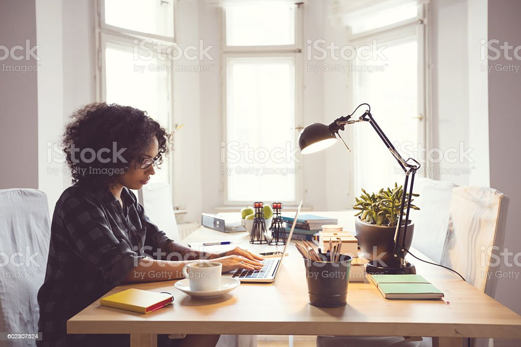 Afro young woman in the home office, using laptop Afro young woman sitting at the table in a home office, using laptop. Adult Stock Photo