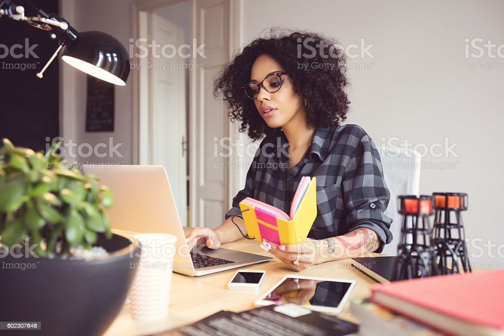 Afro young woman in the home office, using laptop Afro young woman sitting at the desk in a home office, using laptop. Adult Stock Photo