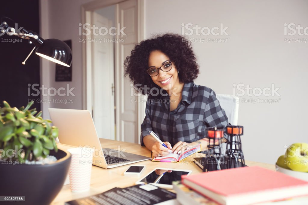 Afro young woman in the home office, using laptop Afro young woman sitting at the desk in a home office, using laptop, smiling at camera. Adult Stock Photo