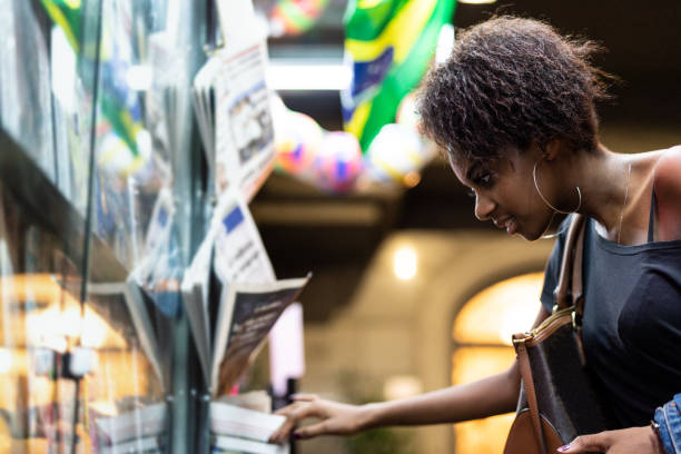 Afro Young Woman looking for the news at newsstand Brazilian woman in Sao Paulo news stand stock pictures, royalty-free photos & images