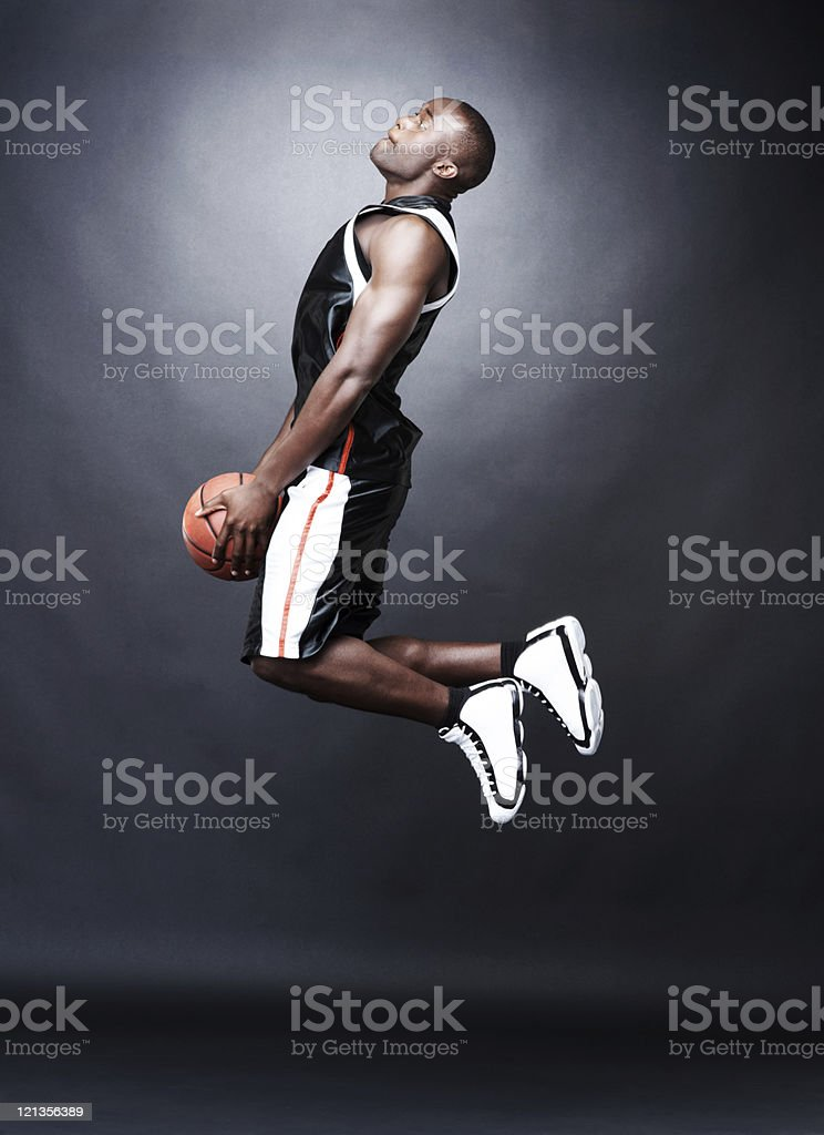 Afroamerican basketball player going for a slam dunk