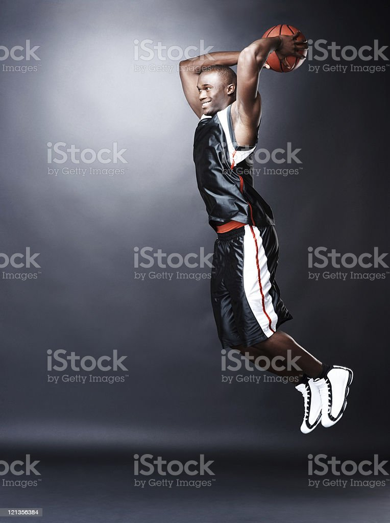 Afro-american basketball player making a dunk shot