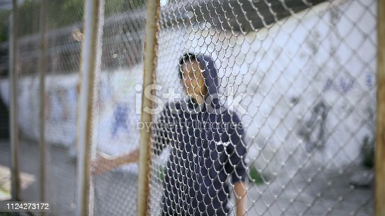 istock Afro-american boy behind fence, migrant child separated from family, detained 1124273172