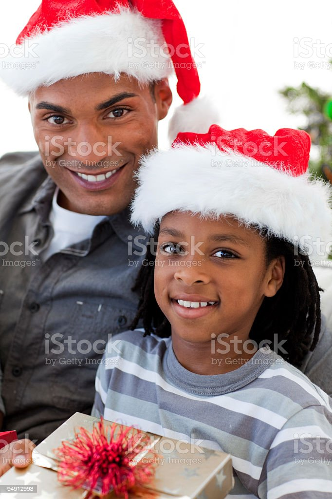 Afro-American father and son holding a Christmas gift royalty-free stock photo