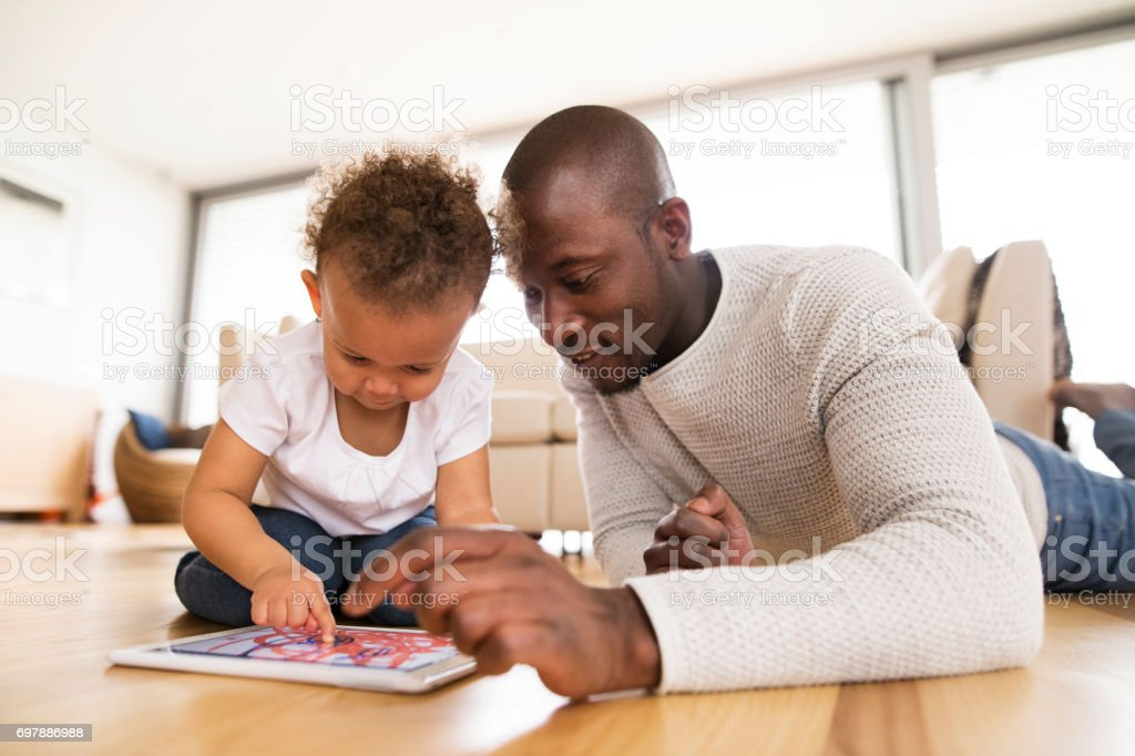Afro-american father with little daughter with tablet at home. stock photo