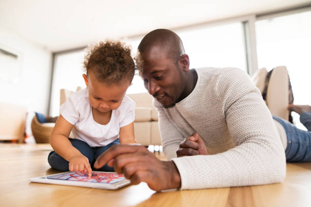 afro-american father with little daughter with tablet at home. - game of life stock photos and pictures
