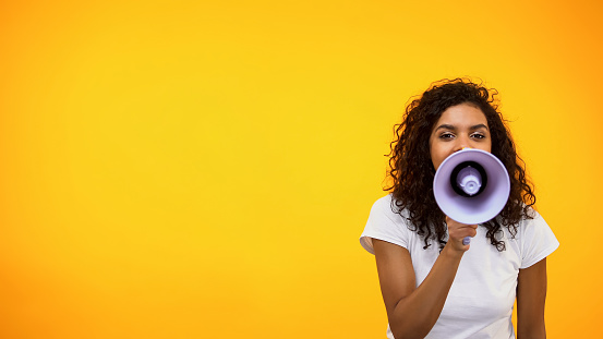istock Afro-American female shouting in megaphone, public relations, social opinion 1152598308