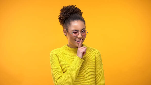 Afro-American lady in eyeglasses showing silence gesture and winkling, flirting Afro-American lady in eyeglasses showing silence gesture and winkling, flirting finger on lips stock pictures, royalty-free photos & images