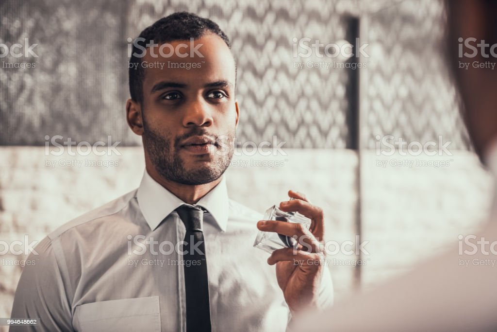 Afro-American Man Applying Perfume in Bathroom. stock photo