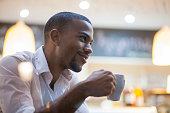 Man in bar holding cup of coffee. Close-up portrait of an afro american man. Photo taken through window.