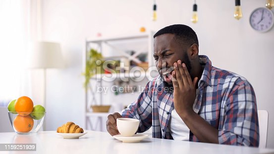 Afro-American man having dental ache, reaction on hot coffee, sensitive teeth
