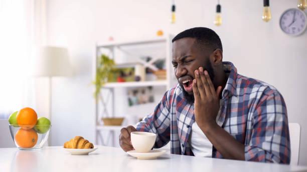 Afro-American man having dental ache, reaction on hot coffee, sensitive teeth stock photo