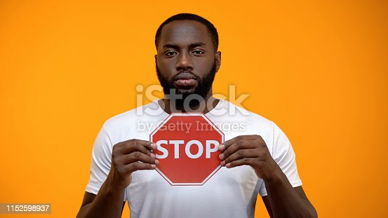 Afro-American man showing stop sign, male against racial discrimination, closeup