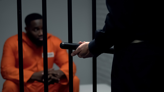 istock Afro-american prisoner in cell looking at jail guard with baton, harassment 1167840184