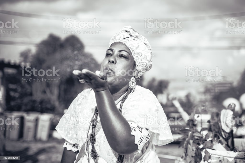 afro-brazilian woman in religious costume blowing powder out of hand stock photo
