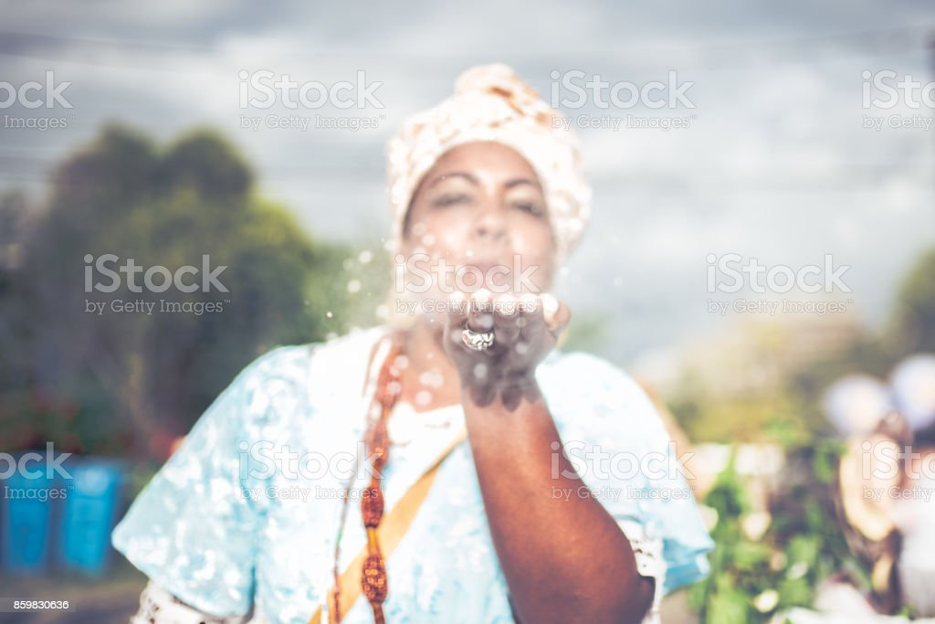 afro-brazilian woman in religious costume blowing white powder out of hand stock photo