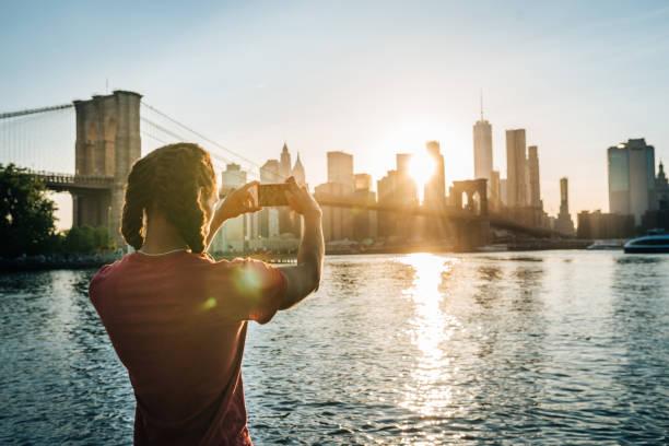 Afro-Karibik, hispanischer Tourist in New York, der bei Sonnenuntergang von Manhattan geschossen wird – Foto