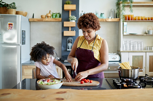 Front view of 3 year old girl interacting with 26 year old mother in kitchen as she slices tomatoes on cutting board for salad and boils water for pasta.