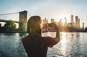 Afro-Caribbean tourist taking sunset shot of New York skyline