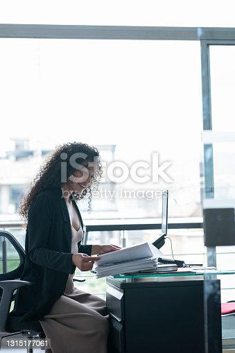 istock Afro-curly Latino businesswoman typing on his computer in a backlight while sitting in his office wearing his formal office clothes 1315177061
