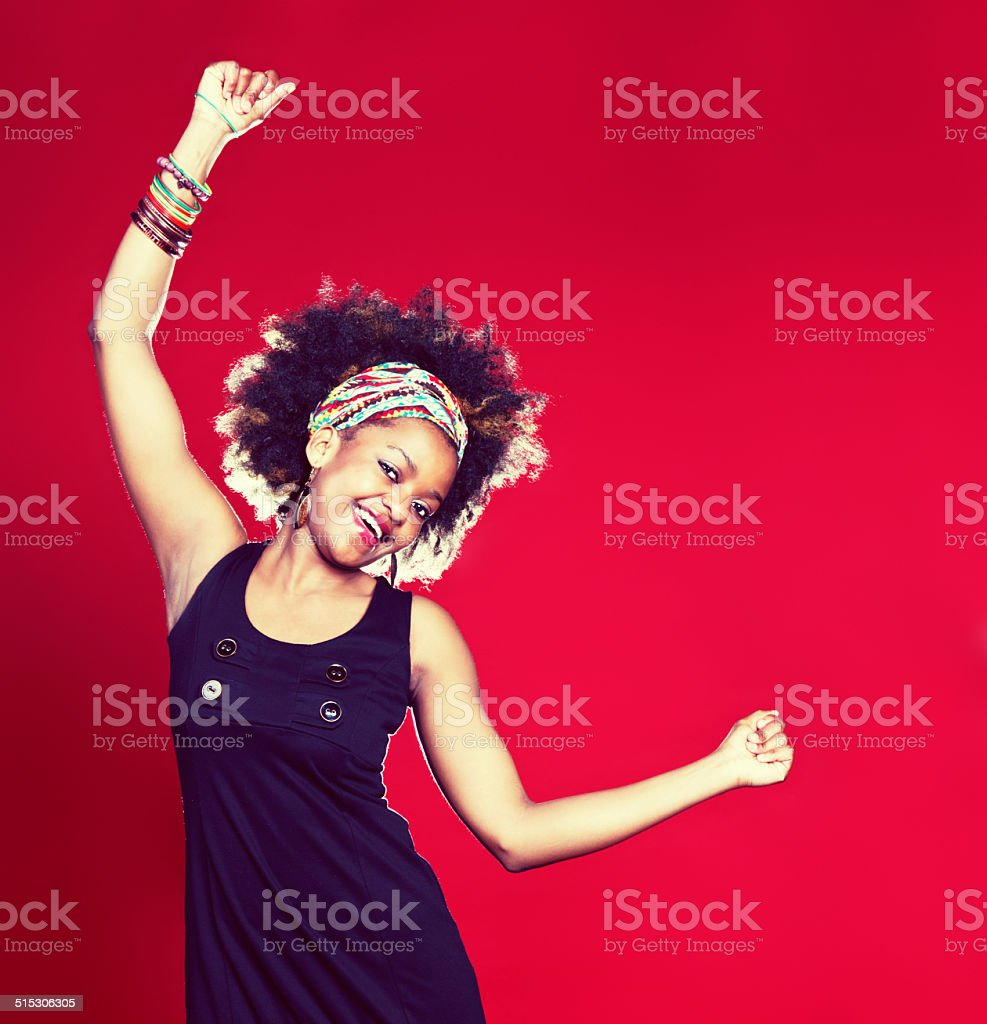 Afro-haired cutie dancing happily on red background stock photo