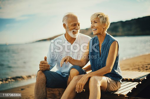 Senior couple sitting on the beach, laughing and talking, enjoying summer vacation.