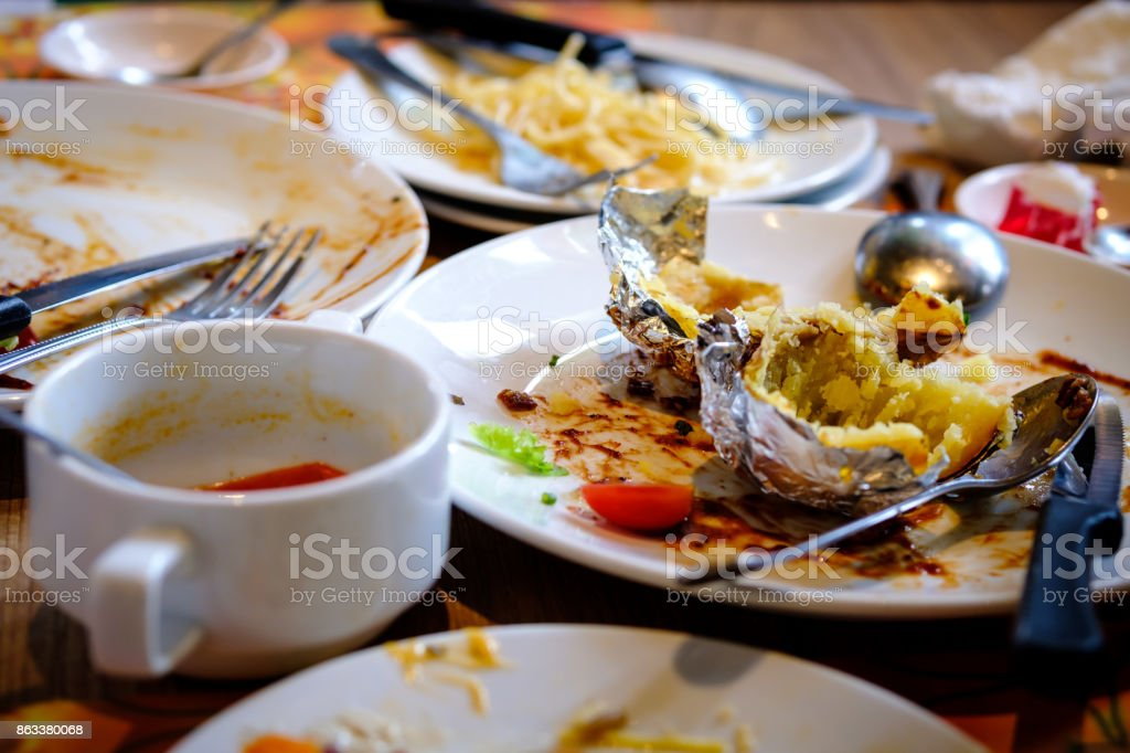 After banquet is finished. Wasted food on served festive table after lunch party. Leftovers, Empty plates, left half eaten food and meals. Dirty empty dish on the table. stock photo