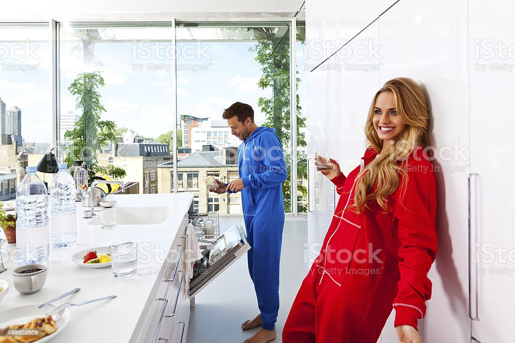 After breakfast Happy young couple standing in the modern kitchen in the morning. Young man putting dishes into dishwasher. 20-24 Years Stock Photo