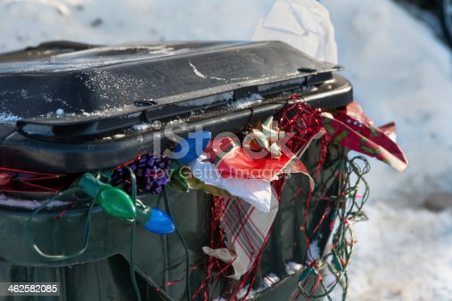 a large plastic trashbin overflowing with garbage and discarded Christmas paper lights bows etc