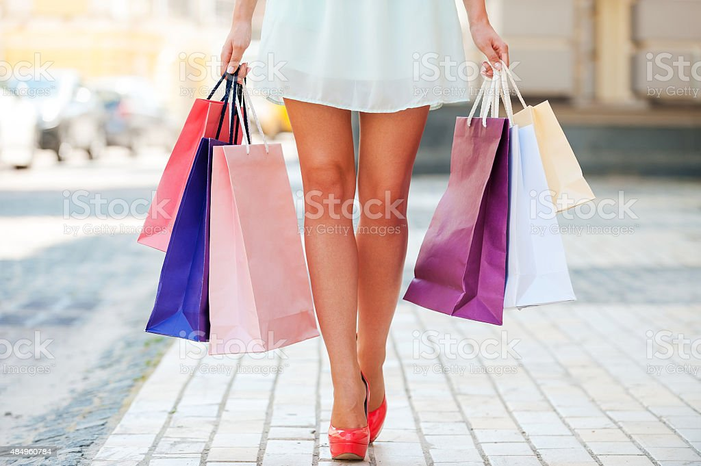 Close-up of young woman carrying shopping bags while walking along...
