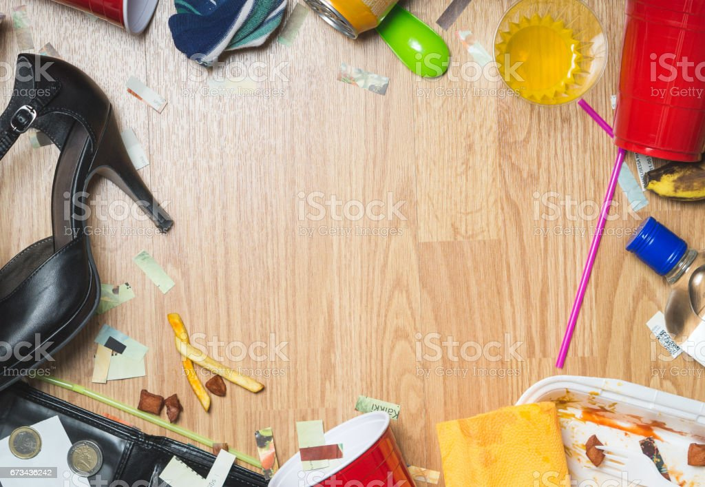 After party and hangover themed background with free empty copy space for text. Wooden floor framed with drinks and trash. stock photo