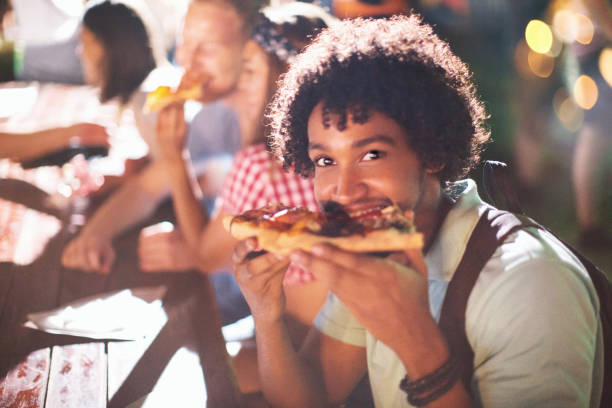 After party food time. Young african american man eating pizza after party. He is smiling and looking at camera. food festival stock pictures, royalty-free photos & images