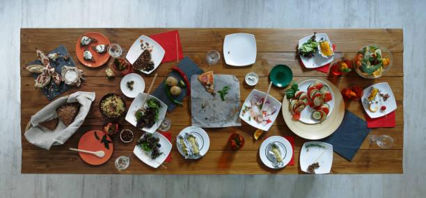 efter fest. bortkastad mat serveras festligt träbord - tallrik uppätet bildbanksfoton och bilder