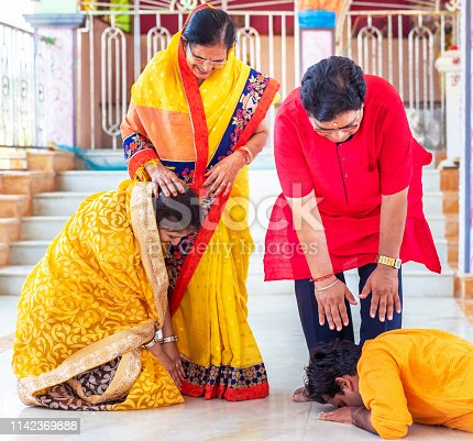 Family, Indian, Hindu, Celebration - Couple Touching Father's feet to obtain blessings after the prayers at a temple