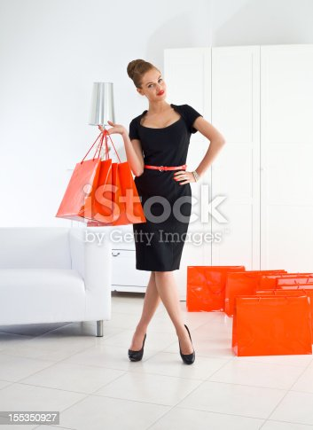 Portrait of beautiful and well-dressed young adult woman standing in her room with many shopping bags, smiling at the camera.