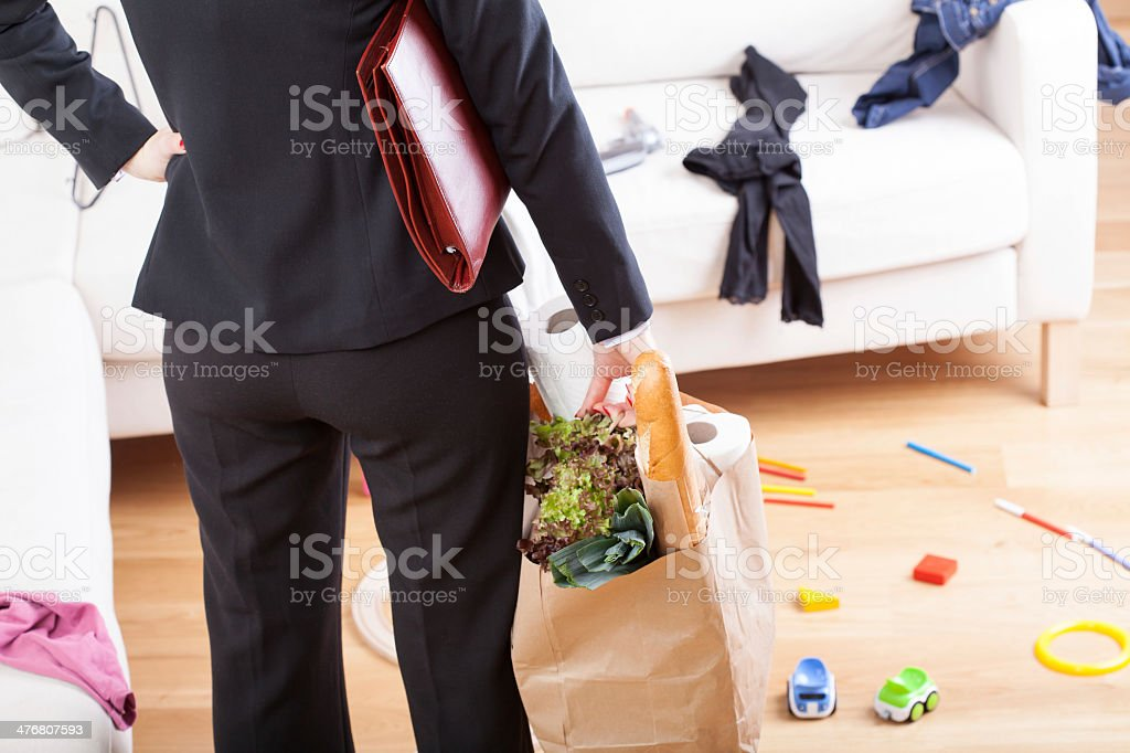 An elegant woman with grocery shopping left in a messy home