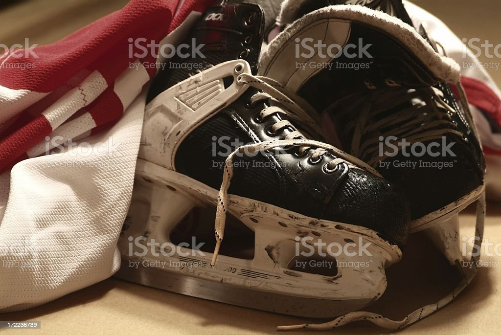 After The Game Close-up of a pair of well worn hockey skates and hockey jersey Aspirations Stock Photo