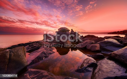 Beautiful pink sunset and rock formation of Brighton beach, Duluth, Minnesota. The reflection of the sky and clouds forms a peaceful picture.