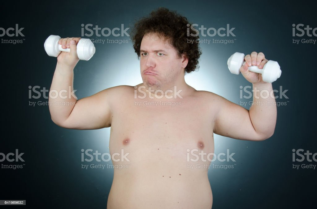 After training. Heavy training. Fat guy with dumbbells. stock photo