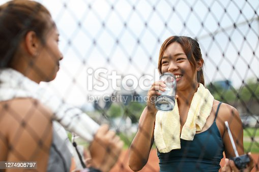 Young team drinking water and chatting beside the protective net of the sports field after exercising