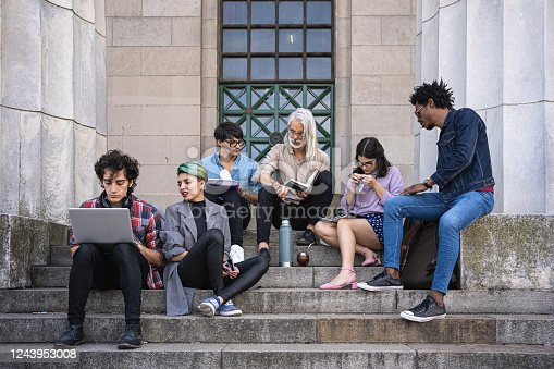 University students sitting on campus stairs, relaxing, talking and bonding while studying with their professor