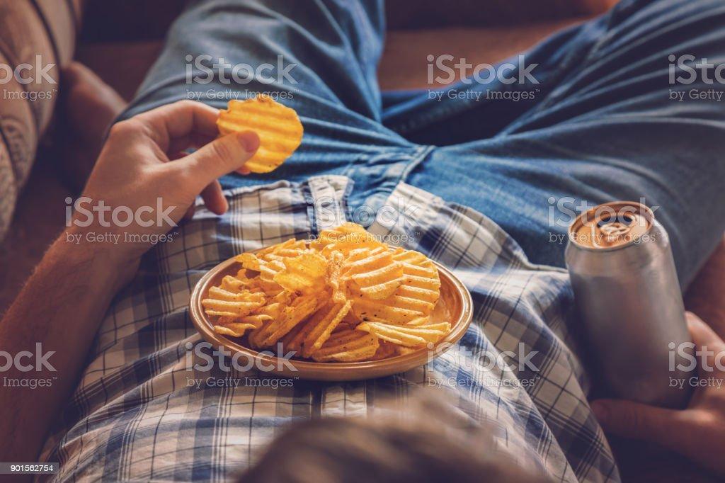 下班後, 一個男人穿著襯衫和牛仔褲躺在沙發上, 喝著冰啤酒, 吃薯片和看體育電視頻道。人的休息時間在家裡的概念。 - 免版稅一個人圖庫照片