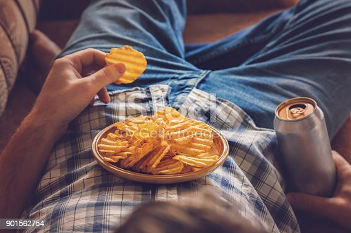 istock After work a guy wearing shirt and jeans lying on sofa, drinking a cold beer, eating crisps and watching sport tv channel. Man's resting time at home concept. 901562754