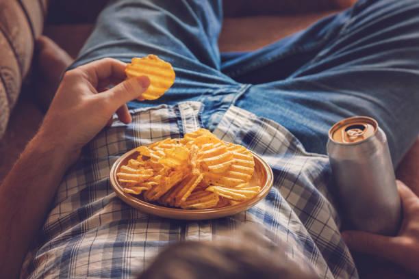 Después de trabajar un chico vestido con camisa y jeans tumbado en el sofá, bebiendo una cerveza bien fría, comiendo patatas fritas y viendo sport tv canal. Hombre de descanso tiempo en concepto de hogar. - foto de stock