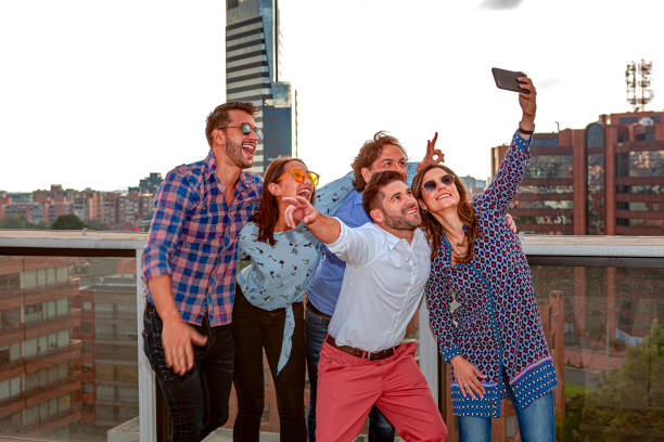 After Work Selfie Time - A Group Of Relaxed, Latin American, Millennial White Collar Workers Seen Hamming For The Mobile Phone Camera; Their Boss Is With Them At The Back. It Will Soon Be On Their Social Media. stock photo