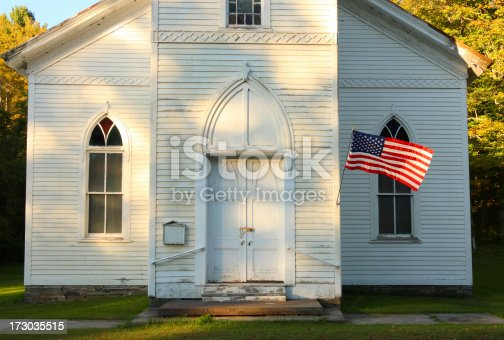 Flag waving in front of old church on summer afternoon.