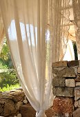 Lacy Curtains lightly blowing with an afternoon breeze in a Tuscan courtyard.